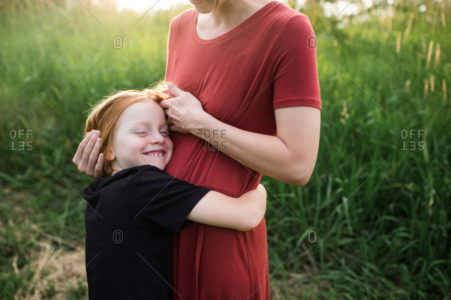 Boy hugging his mother around the waist