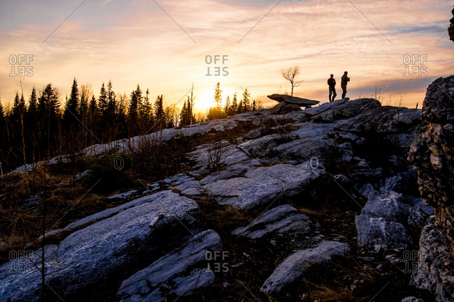 Silhouette of friends on top of rocks at sunset, Bolshoy Ural, Sverdlovsk, Russia, Europe