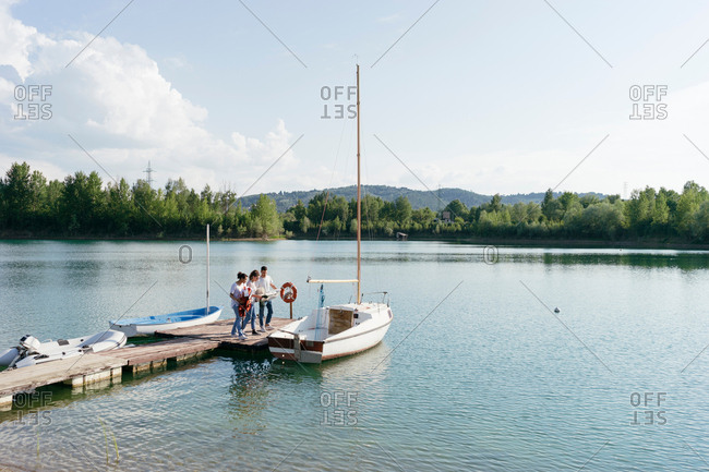 Friends standing on pier, boarding sailing boat
