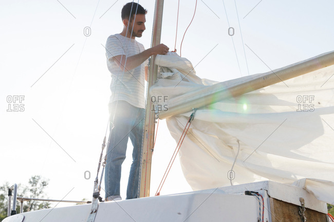 Man on sailing boat, preparing to hoist sail