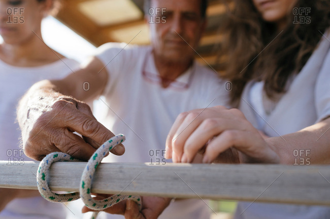 Man showing women how to tie nautical knot, close-up