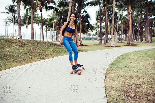 Young woman skateboarding through park, smiling, South Point Park, Miami Beach, Florida, USA