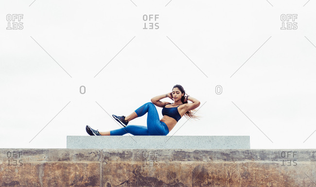 Young woman exercising outdoors, doing sit-ups, South Point Park, Miami Beach, Florida, USA