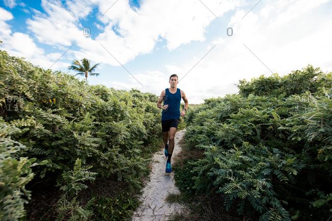 Young man exercising, running outdoors, South Point Park, Miami Beach, Florida, USA