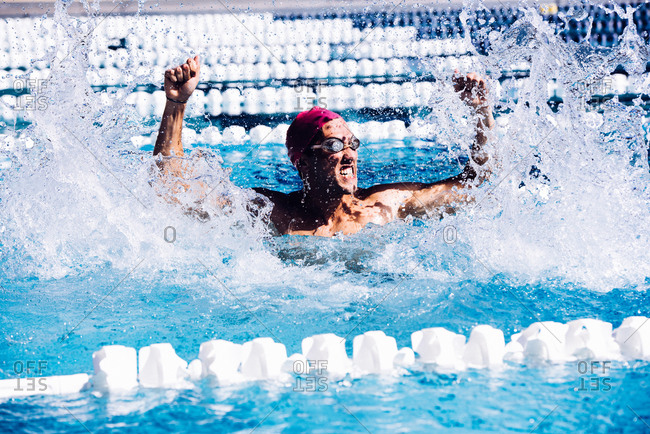 Swimmer in pool beating water in triumph