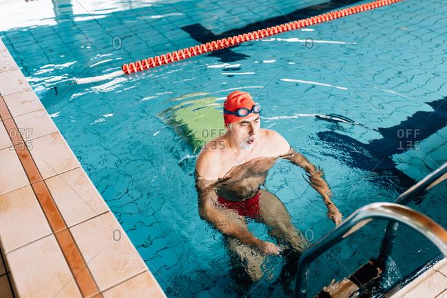 Senior man using ladder in swimming pool