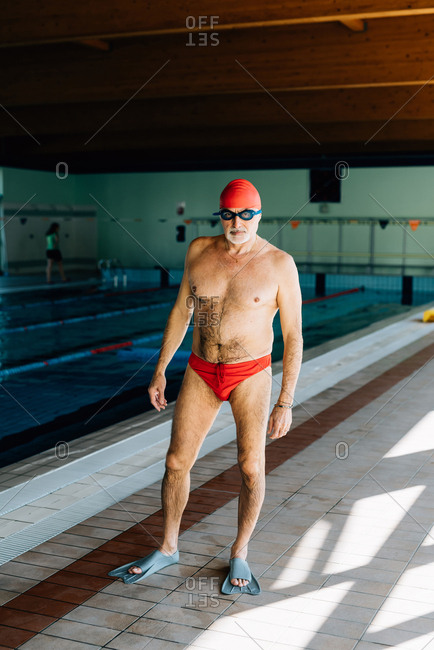 Senior man standing by swimming pool