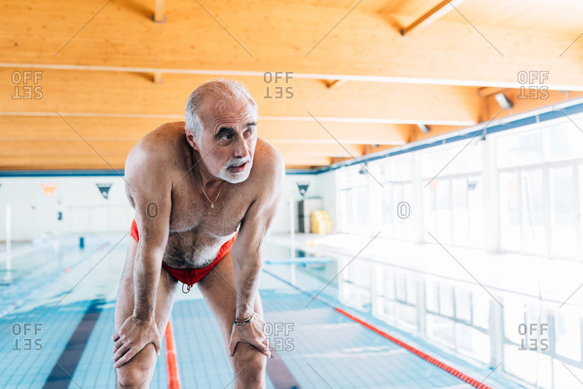 Senior man bending over catching his breathe by pool