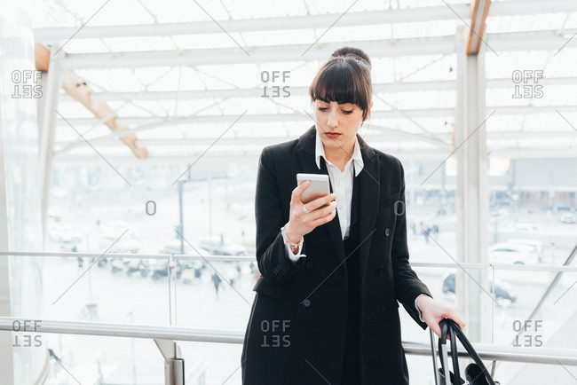 Businesswoman using mobile phone on business trip, Milan, Italy