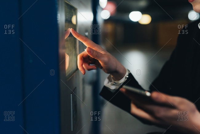 Businesswoman using ticket machine, Milan, Italy