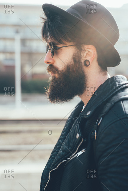 Young male hipster in sunglasses and trilby at city tram station