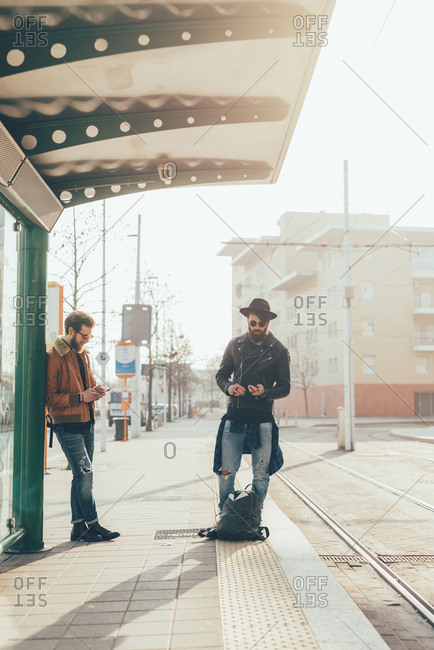 Two young male hipsters looking at smartphones while waiting at city tram station