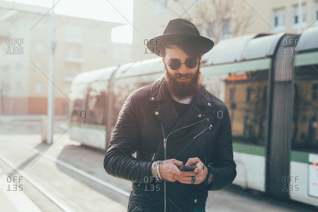 Young male hipster looking at smartphones  at city tram station