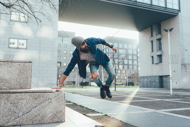 Young male hipster jumping mid air practicing parkour in city