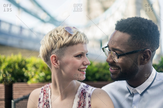 Young couple outdoors, face to face, smiling