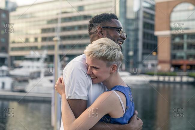 Young couple beside dock, hugging