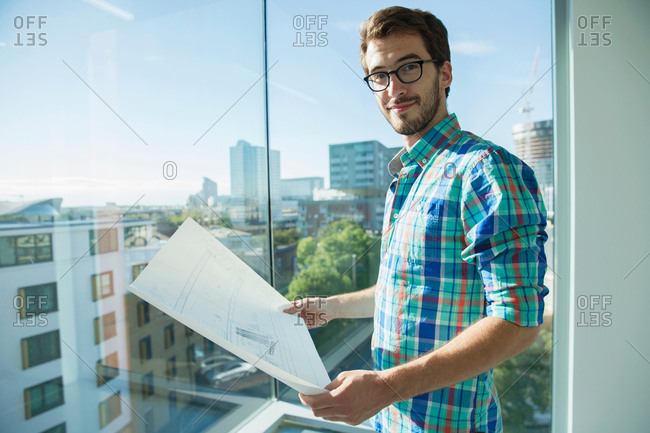 Portrait of man, standing beside office window, looking at plans