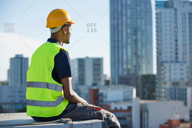 Construction worker sitting on ledge, outdoors, taking a break
