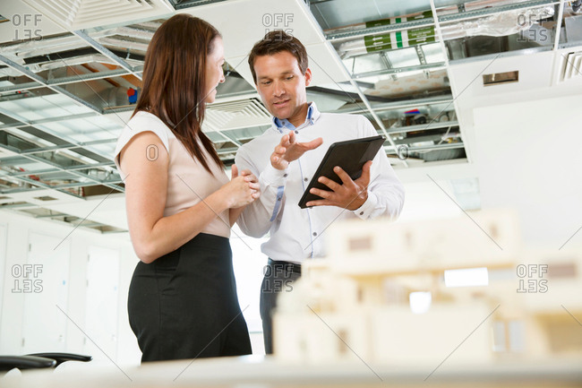 Businessman and woman having discussion, looking at digital table, architectural model on tablet, low angle view