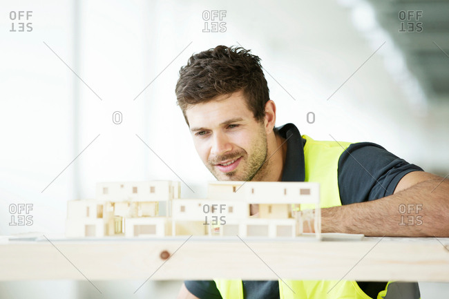 Man wearing hi vis vest, looking at model of building