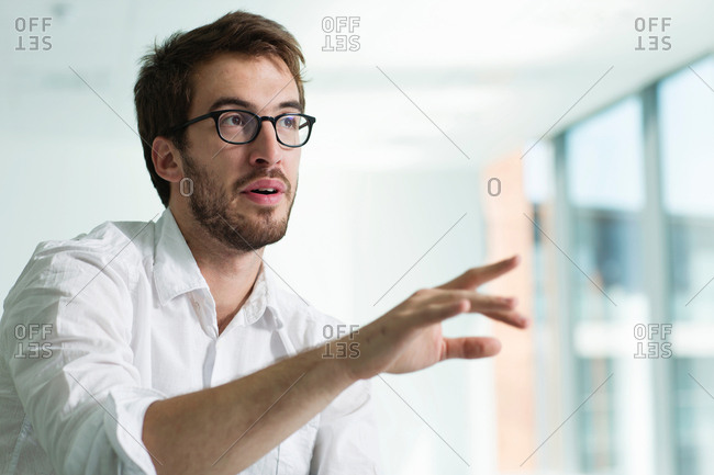 Portrait of businessman, hand raised in conversation
