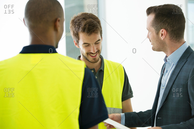 Two men wearing hi vis vests, having discussion with businessman