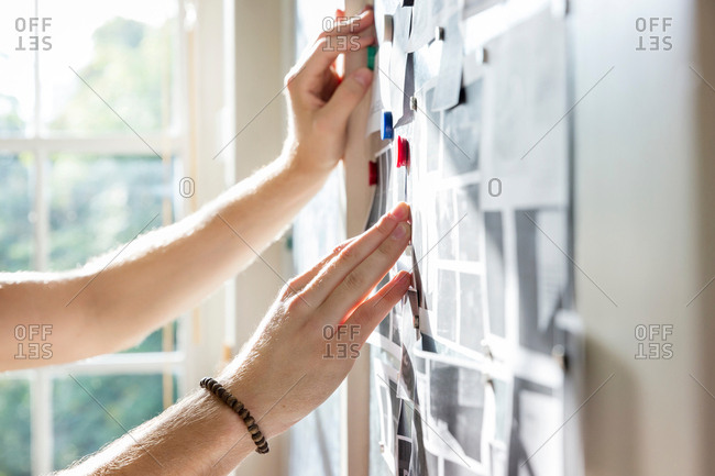 Hands of male designer pinning mood board ideas to wall in creative studio