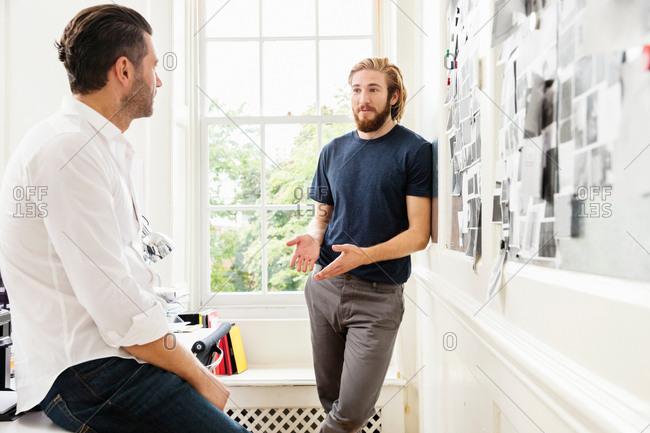 Young male designer explaining mood board idea to colleague in creative studio