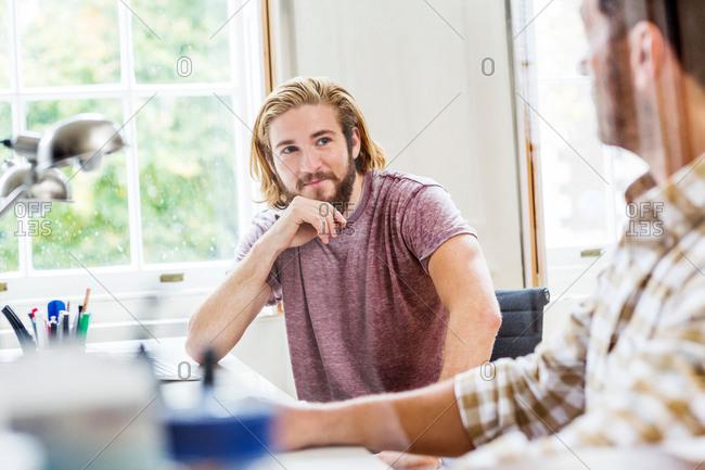 Two male designers having discussion at desk in creative studio
