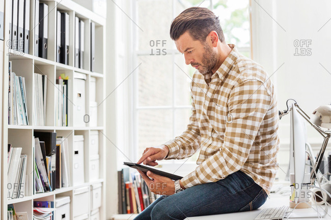 Male designer using digital tablet touchscreen in creative studio