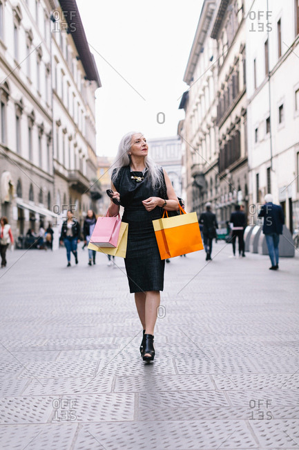 Stylish mature female shopper strolling down street, Florence, Italy