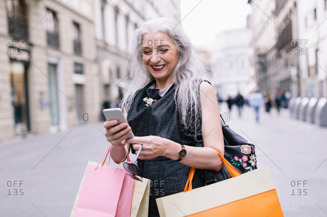 Stylish mature female shopper looking at smartphone on street, Florence, Italy