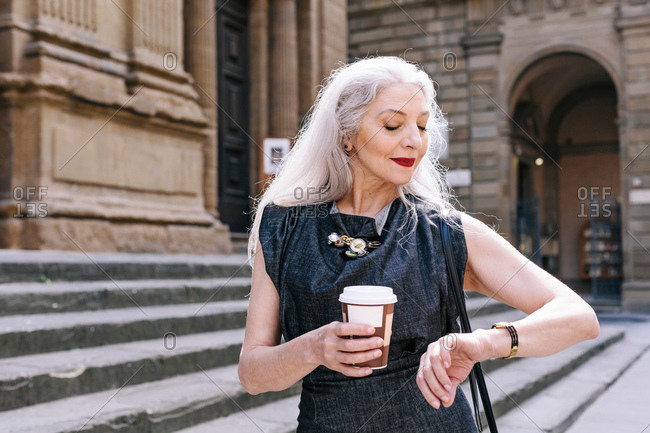 Mature woman with long grey hair looking at wristwatch in Florence, Italy