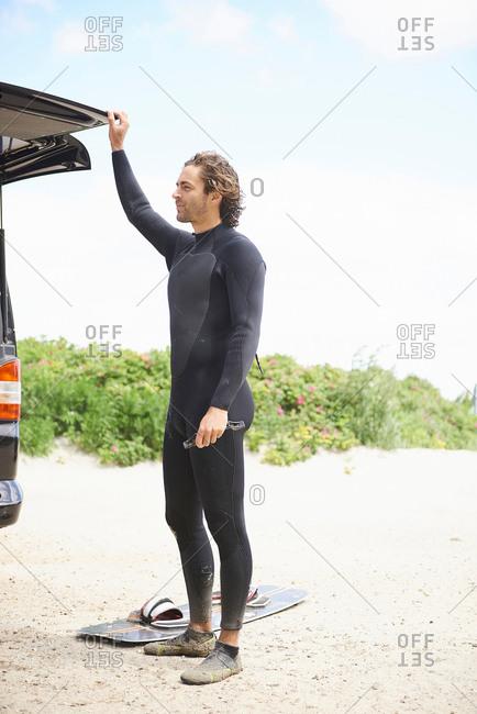 Kite surfer in wetsuit by car boot, Hornbaek, Hovedstaden, Denmark