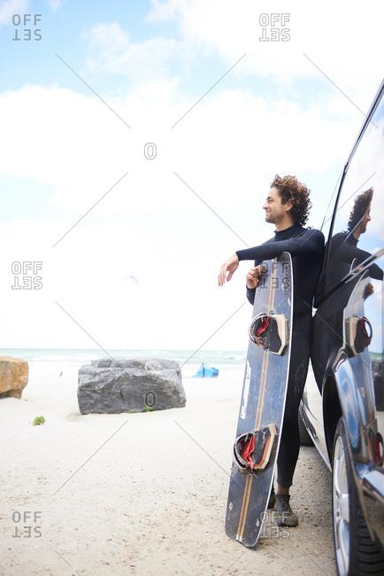 Kite surfer in wetsuit leaning against car, Hornbaek, Hovedstaden, Denmark