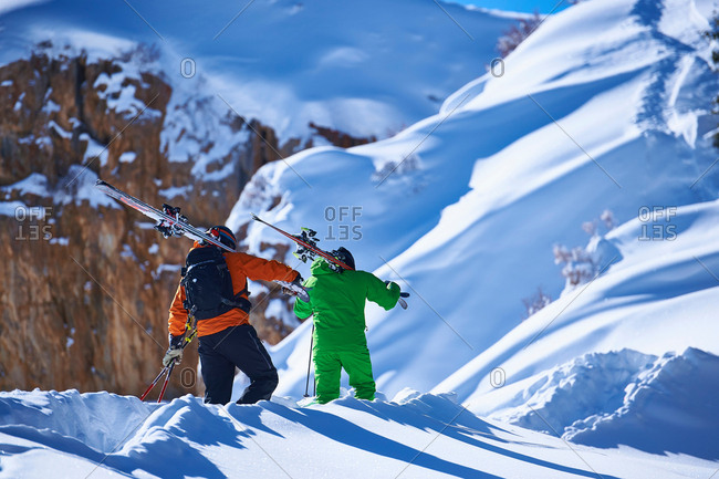 Two male skiers trudging up deep snow covered mountain, Aspen, Colorado, USA