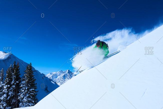 Man skiing down steep snow covered mountainside, Aspen, Colorado, USA