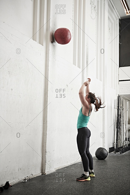 Woman throwing fitness ball against wall in cross training gym