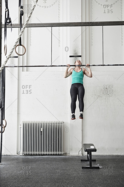 Woman doing chin-up in cross training gym