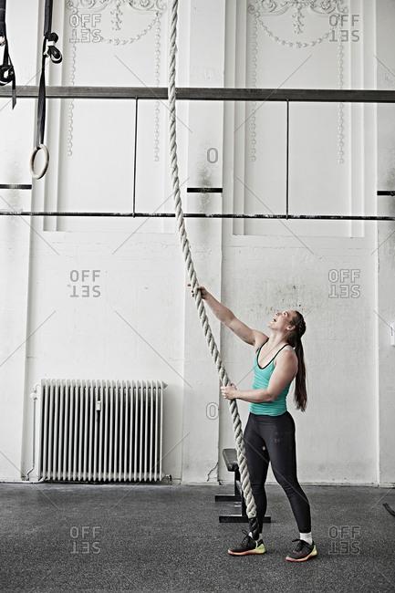 Woman rope climbing in cross training gym