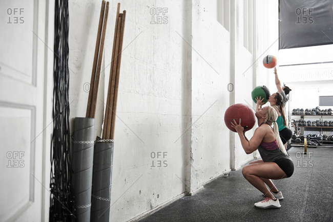 Friends throwing fitness ball against wall in cross training gym