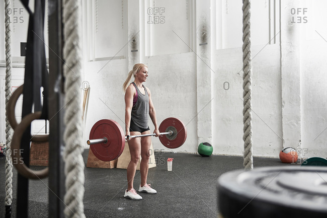 Woman lifting barbell in cross training gym