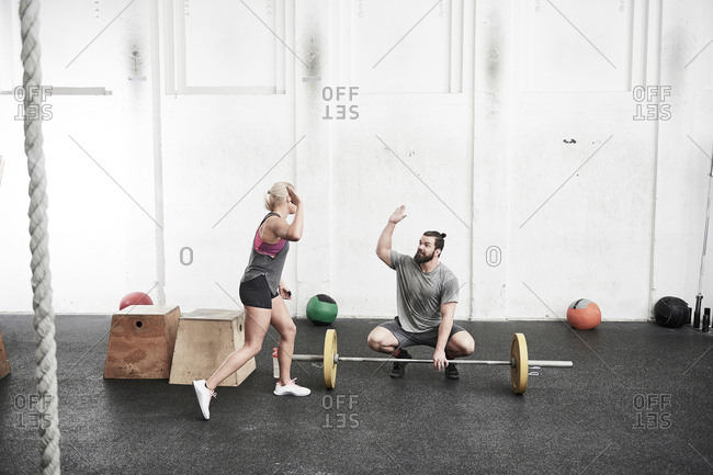 Couple giving high five in cross training gym