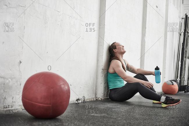 Woman taking break in cross training gym