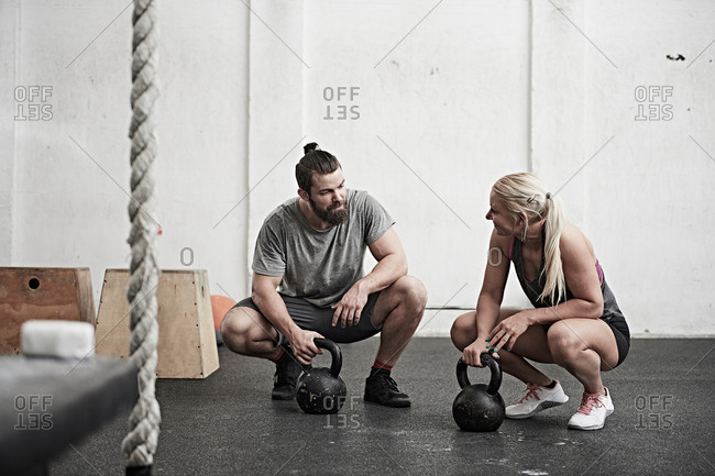 Couple with kettle bells in cross training gym