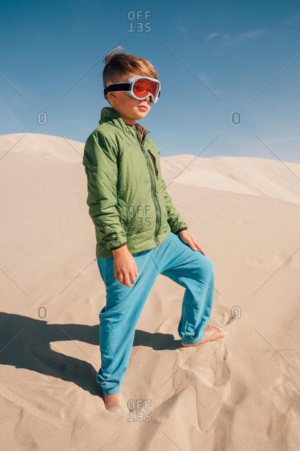 Portrait of boy on sand dunes, wearing goggles, Eureka Dunes, Death Valley National Park, California, USA