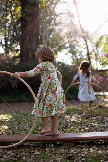 Sisters playing with plastic hoops in shaded garden
