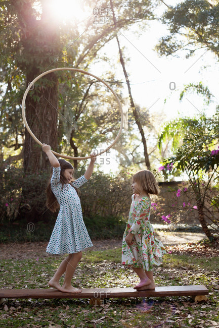 Sisters playing with hula hoop in shaded garden