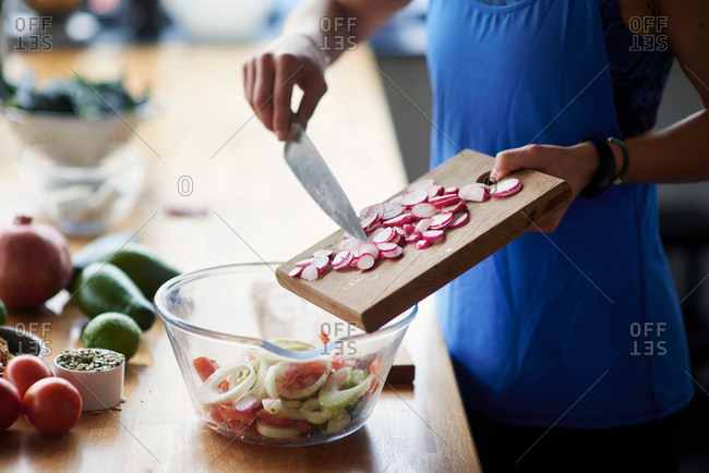 Mid section of young woman at kitchen table preparing sliced radish