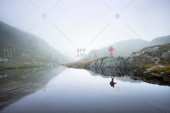 Male hiker hiking along foggy riverbank, Gros Morne National Park, Newfoundland, Canada